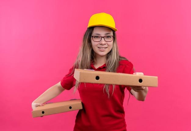 赤いポロシャツと黄色い帽子の若い配達の女の子は、カメラの笑顔に伸びるピザの箱を保持しています