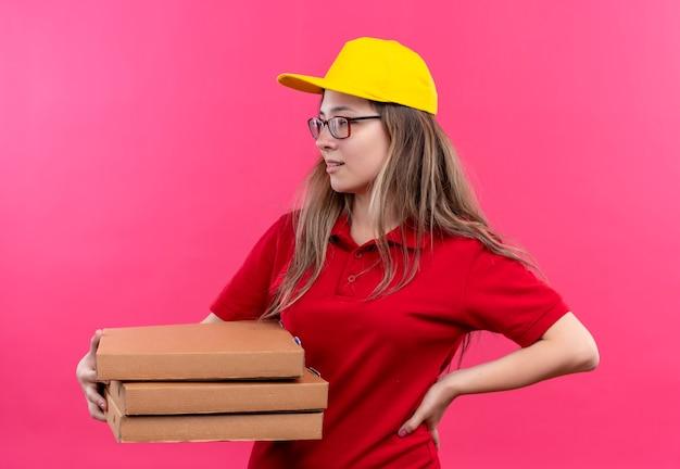 Молодая доставщица в красной рубашке поло и желтой кепке держит стопку коробок для пиццы, глядя в сторону с уверенным выражением лица