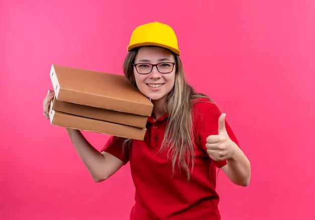 赤いポロシャツと黄色い帽子の若い配達の女の子は、親指を上手に見せて元気に笑っているカメラを見てピザボックスのスタックを保持しています