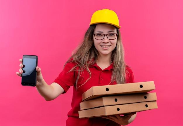 赤いポロシャツと黄色い帽子の若い配達の女の子は、スマートフォンを示す顔に自信を持って笑顔でカメラを見てピザボックスのスタックを保持しています