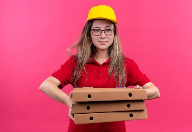 顔に自信を持って笑顔でカメラを見てピザボックスのスタックを保持している赤いポロシャツと黄色の帽子の若い配達の女の子