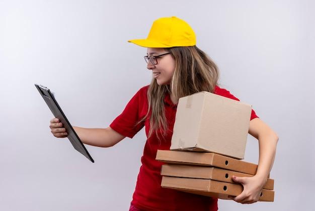 Молодая доставщица в красной рубашке поло и желтой кепке держит стопку коробок для пиццы, смотрит в буфер обмена другой рукой и выглядит смущенной