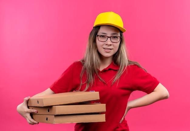 自信を持って見えるピザの箱のスタックを保持している赤いポロシャツと黄色の帽子の若い配達の女の子