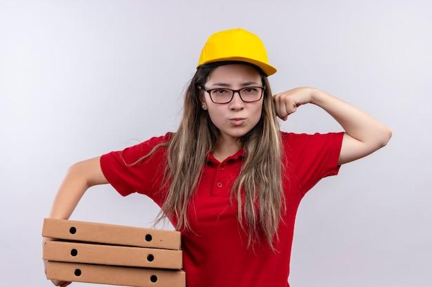 赤いポロシャツと黄色い帽子の上腕二頭筋を示す拳を上げるピザボックスのスタックを保持している若い配達の女の子、勝者の概念