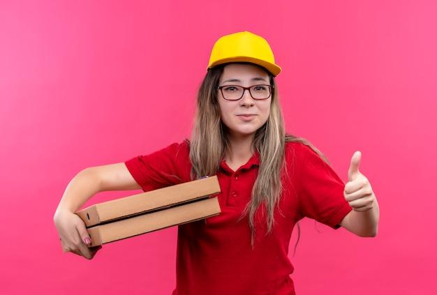 赤いポロシャツと黄色い帽子の若い配達の女の子は、親指を上げて笑っているピザの箱のスタックを保持しています