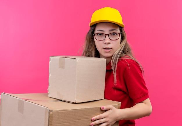 赤いポロシャツと黄色の帽子を保持している若い配達の女の子
