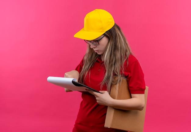 クリップボード保持ボックスパッケージの空白のページを見て赤いポロシャツと黄色の帽子の若い配達の女の子