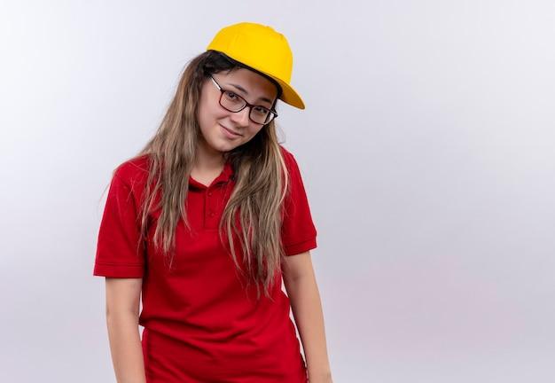 恥ずかしがり屋の表情を持って笑顔のカメラを見て赤いポロシャツと黄色の帽子の若い配達の女の子