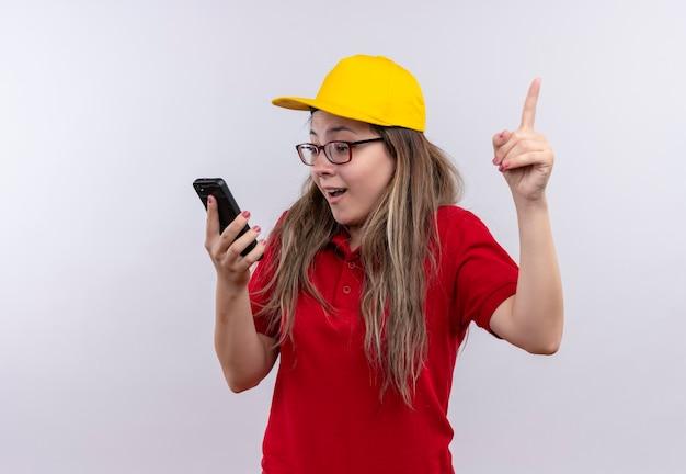 赤いポロシャツと黄色い帽子をかぶった若い配達の女の子が画面を見ていますああ彼女のスマートフォンは人差し指を上に向けて新しい素晴らしいアイデアを持っています