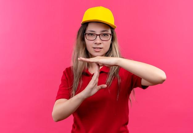 Молодая доставщица в красной рубашке поло и желтой кепке выглядит усталой, нуждается в перерыве, делая тайм-аут руками