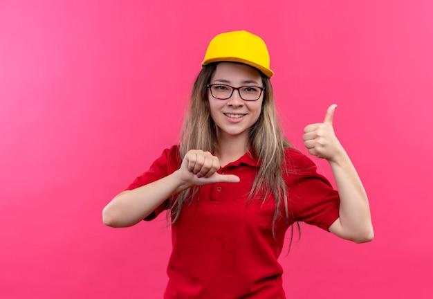 赤いポロシャツと黄色い帽子をかぶった若い配達の女の子は、自分自身に満足し、笑顔で親指を誇らしげに指しています
