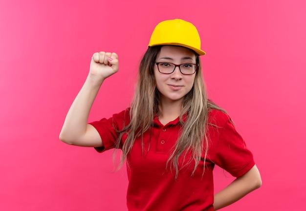 赤いポロシャツと黄色のキャップの若い配達の女の子ポジティブで幸せな握りこぶし、勝者の概念