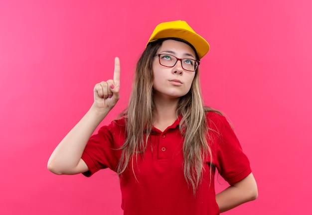 新しいアイデアを持っている人差し指を示す赤いポロシャツと黄色のキャップの若い配達の女の子