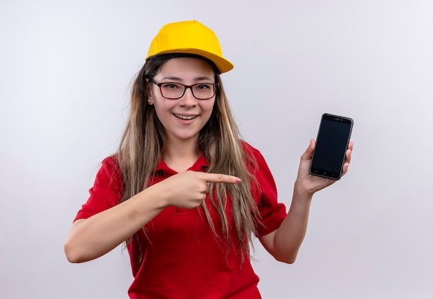 赤いポロシャツと黄色い帽子の若い配達の女の子は、元気に笑ってそれに指で指しているスマートフォンを示しています