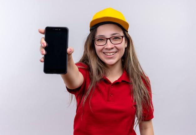 赤いポロシャツと黄色い帽子の若い配達の女の子は、広く笑顔でスマートフォンをカメラに見せています