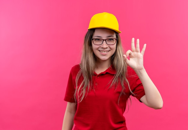 赤いポロシャツと黄色い帽子の若い配達の女の子は大丈夫サインを示して広く笑っています