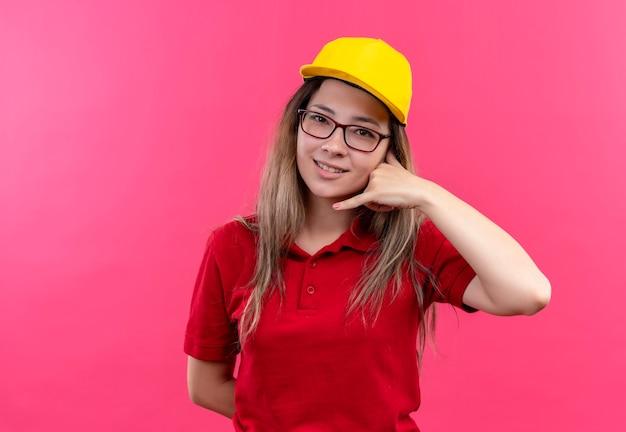赤いポロシャツと黄色い帽子の若い配達の女の子が笑顔で私をジェスチャーと呼んでいます