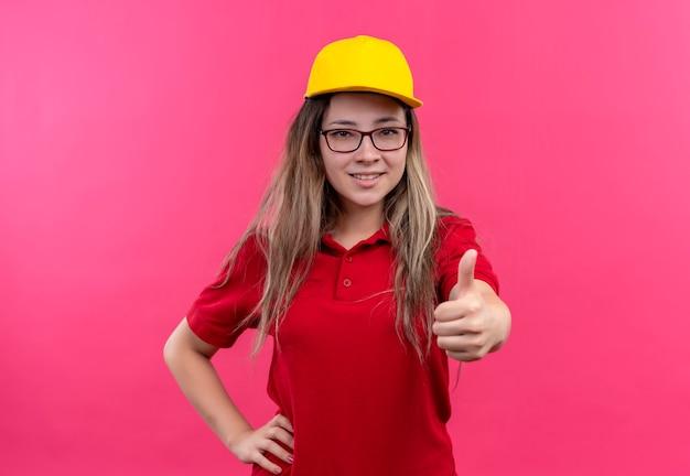 赤いポロシャツと黄色い帽子の若い配達の女の子は親指を見せて笑っている