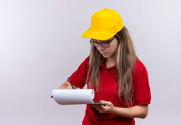 赤いポロシャツと黄色い帽子の若い配達の女の子が空白のページに何かを書いています
