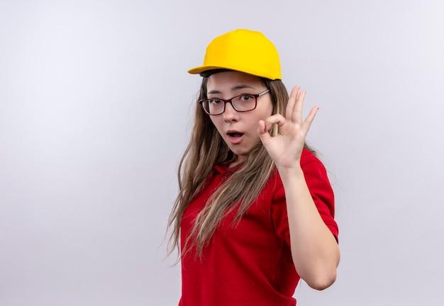赤いポロシャツと黄色のcapexitedとokサインをやって幸せの若い配達の女の子