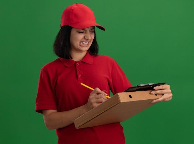 빨간색 유니폼과 모자를 들고 젊은 배달 소녀 연필로 뭔가 쓰는 연필로 피자 상자와 클립 보드를 들고 녹색 벽 위에 서서 불쾌하고 혼란스러워