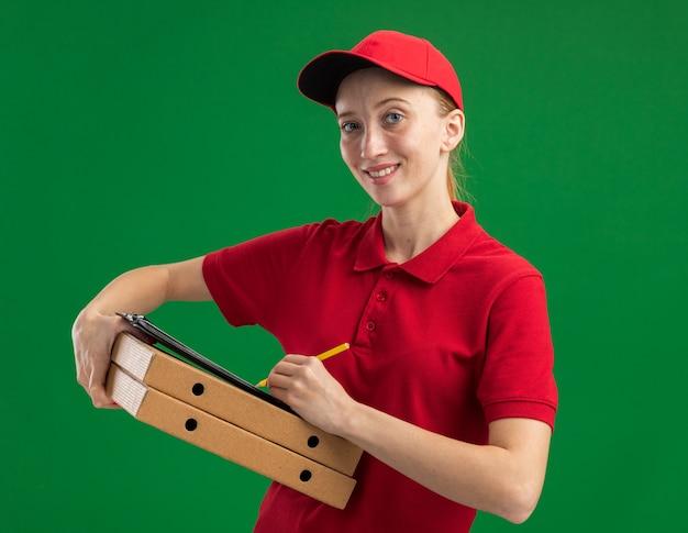 빨간 제복을 입은 젊은 배달 소녀와 녹색 벽 위에 자신감이 서있는 연필로 빈 페이지와 피자 상자와 클립 보드를 들고 모자
