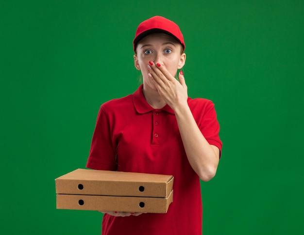 빨간 유니폼과 모자를 들고 젊은 배달 소녀 녹색 벽 위에 서있는 손으로 입을 덮고 충격을 받고 피자 상자를 들고