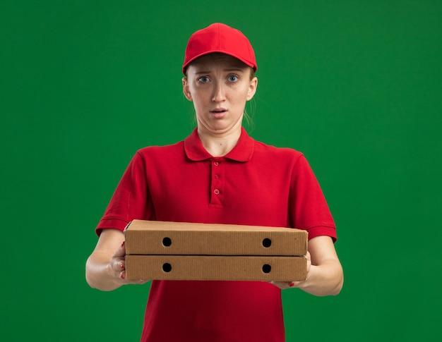 빨간 제복을 입은 젊은 배달 소녀와 피자 상자를 들고 모자는 녹색 벽 위에 서서 혼란스럽고 놀란다.