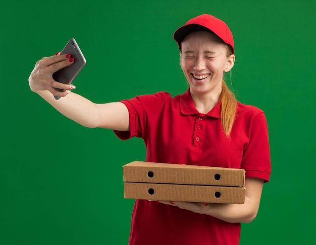 빨간 제복을 입은 젊은 배달 소녀와 모자는 녹색 벽 위에 유쾌하게 서있는 스마트 폰을 사용하여 셀카를하고 피자 상자를 들고