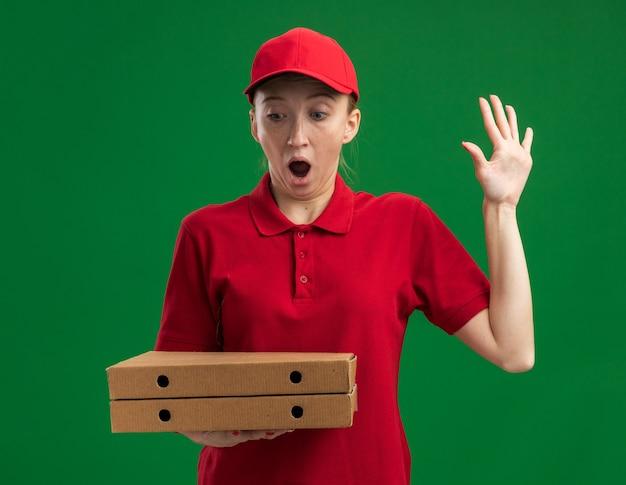 빨간 제복을 입은 젊은 배달 소녀와 피자 상자를 들고 모자는 녹색 벽 위에 서있는 팔을 올려 놀라게했습니다.