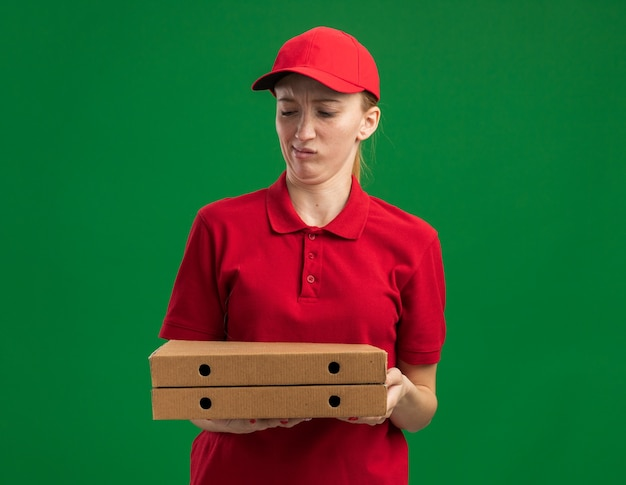 빨간 제복을 입은 젊은 배달 소녀와 피자 상자를 들고 모자를 쓰고 혼란스럽고 불쾌한 녹색 벽 위에 서서