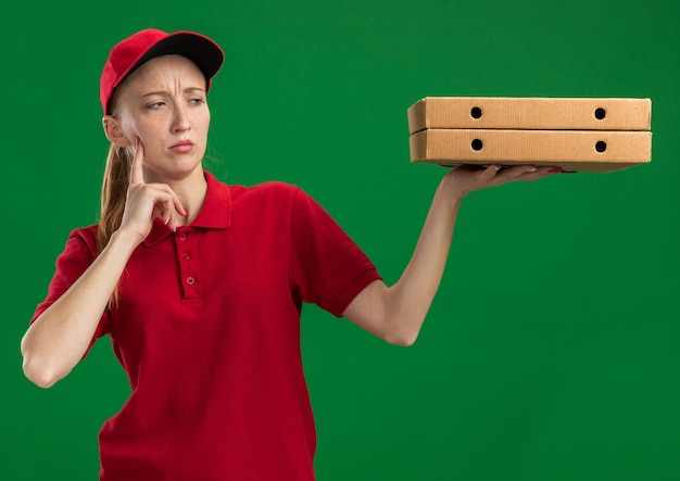 빨간 제복을 입은 젊은 배달 소녀와 그들을보고 피자 상자를 들고 모자 녹색 벽 위에 서 의아해