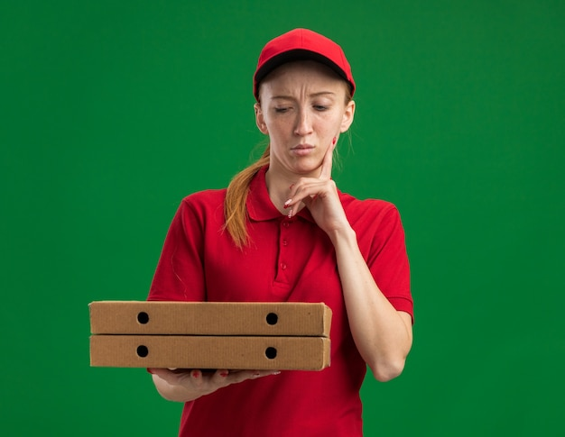 빨간 제복을 입은 젊은 배달 소녀와 녹색 벽 위에 서있는 턱에 손가락으로 의아해 피자 상자를 들고 모자