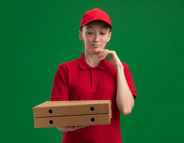 빨간 제복을 입은 젊은 배달 소녀와 녹색 벽 위에 서있는 턱 생각에 손으로 그들을보고 피자 상자를 들고 모자