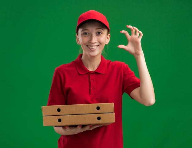 빨간 제복을 입은 젊은 배달 소녀와 모자는 녹색 벽 위에 유쾌하게 서있는 손가락으로 작은 크기의 제스처를 만드는 피자 상자를 들고