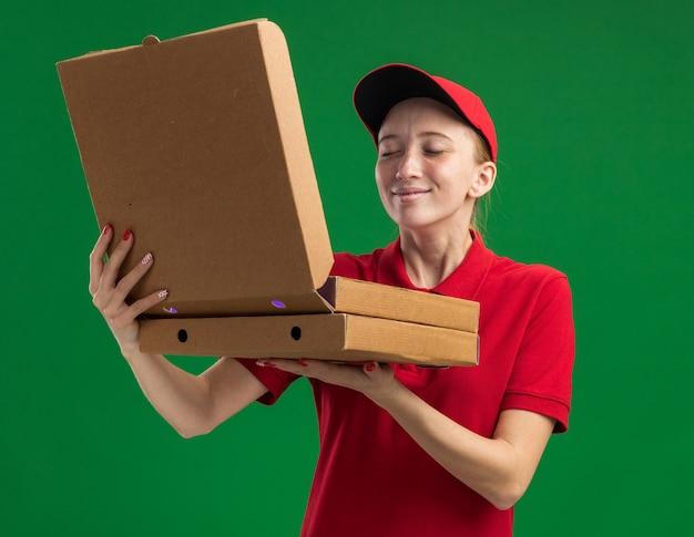 빨간 제복을 입은 젊은 배달 소녀와 녹색 벽 위에 서있는 즐거운 향기를 흡입하는 상자 중 하나를 여는 피자 상자를 들고 모자