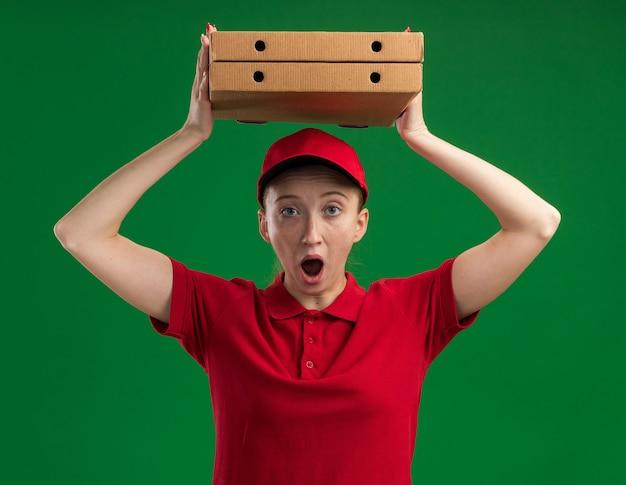 빨간 유니폼과 모자에 젊은 배달 소녀 머리 위에 피자 상자를 들고 놀라게하고 녹색 벽 위에 서 놀란