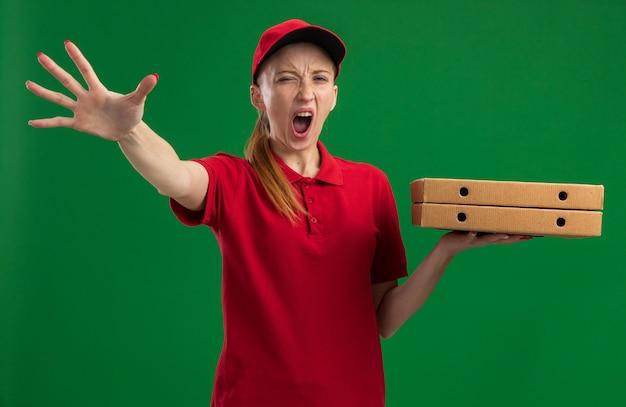 Молодая доставщица в красной униформе и кепке держит коробки для пиццы и кричит с агрессивным выражением лица, делая жест остановки рукой, стоящей над зеленой стеной
