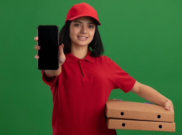 Молодая доставщица в красной форме и кепке держит коробки для пиццы, показывая смартфон с улыбкой на лице, стоящим над зеленой стеной
