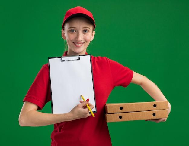 빨간 제복을 입은 젊은 배달 소녀와 모자는 서명을 요구하는 연필로 자신감을 보여주는 클립 보드 미소 피자 상자를 들고