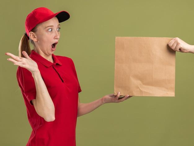 Молодая доставщица в красной форме и кепке с удивленным выражением лица