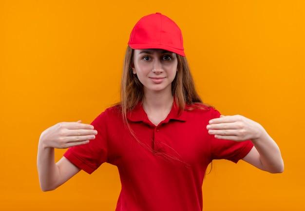 赤い制服を着た若い配達の女の子は、孤立したオレンジ色の壁に何かを持っているふりをします