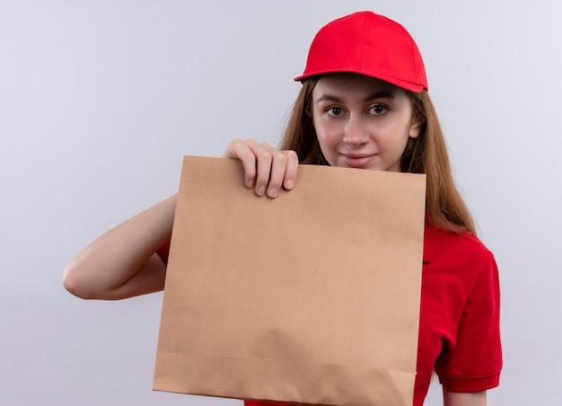 Молодая доставщица в красной форме показывает бумажный пакет и на изолированной белой стене
