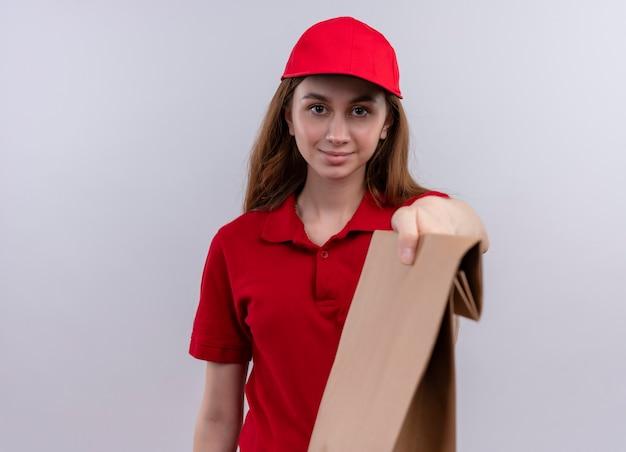 Молодая доставщица в красной форме, растягивая бумажный пакет и на изолированной белой стене с копией пространства
