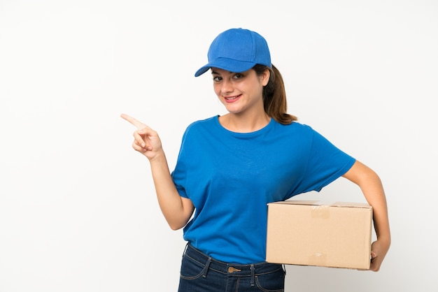 Young delivery girl over isolated white  pointing finger to the side