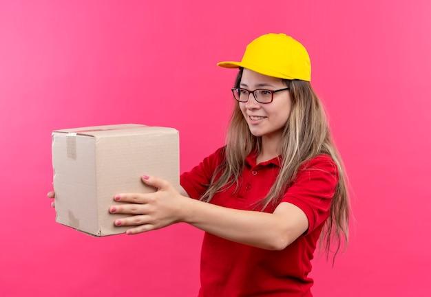 Giovane ragazza di consegna in camicia di polo rossa e cappuccio giallo che tiene il pacchetto della scatola dandolo a un cliente sorridente amichevole
