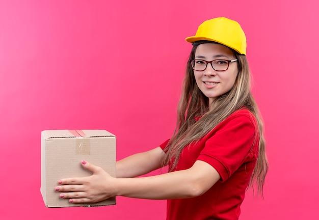Giovane ragazza di consegna in camicia di polo rossa e cappuccio giallo che tiene il pacchetto della scatola dandolo a un cliente con un sorriso fritto