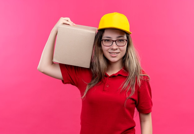 Young delivery girl in red polo shirt and yellow cap holding box package looking at camera smiling confident