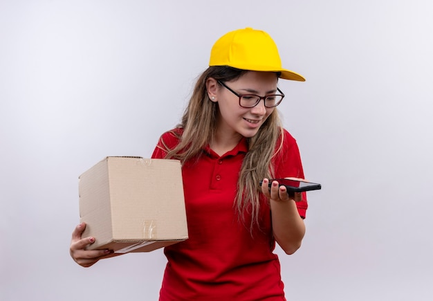 Young delivery girl in red polo shirt and yellow cap holding box package looking at screen of her smartphone sending voice message