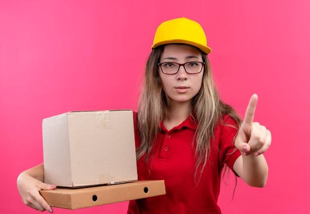 Giovane ragazza di consegna in camicia di polo rossa e cappuccio giallo che tiene le scatole di cartone che mostrano il dito indice